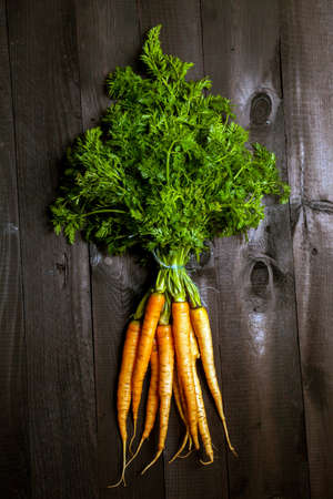 Bunch of ripe carrots on a black wooden background photo