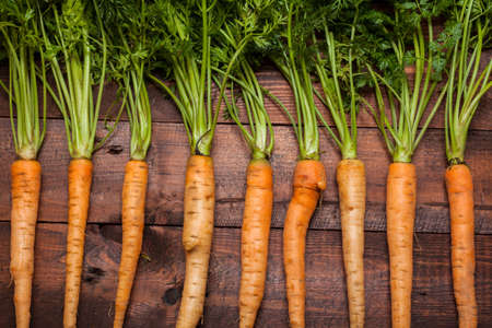 Bunch of ripe carrots on a brown wooden background photo