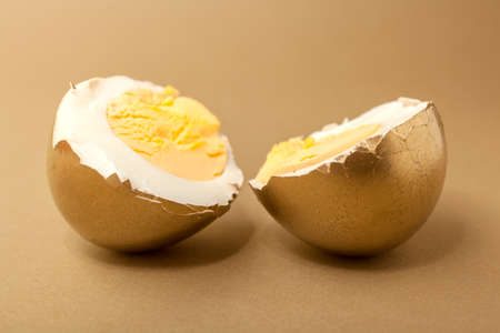Boiled egg cut in two pieces, painted gold over beige background photo