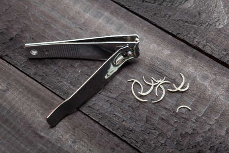 Nail clipper and some nail clippings over a dark wooden surface photo