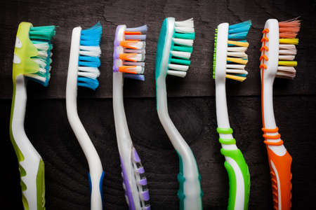 Colorful toothbrushes on black wooden background Stock Photo - 27056688