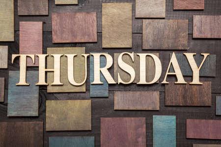 Wooden letters forming word THURSDAY written on wooden background photo