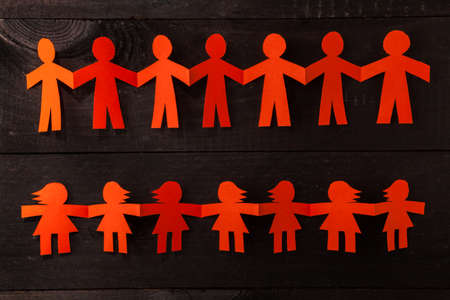 Group of paper doll holding hands. Teamwork concept papercraft. Orange dolls on black wooden background photo