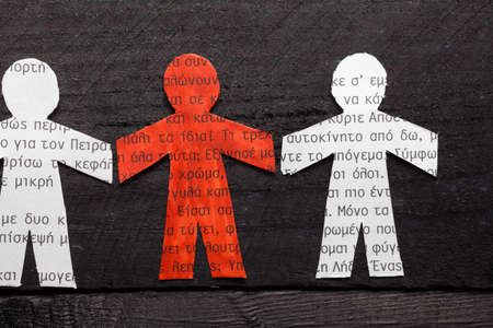 Clipped paper doll with Greek text on wooden black background. Stands out the red one photo
