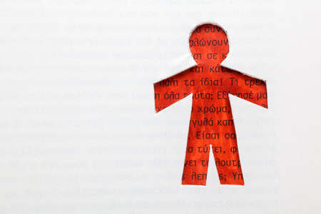 Clipped paper doll within a book with Greek text photo