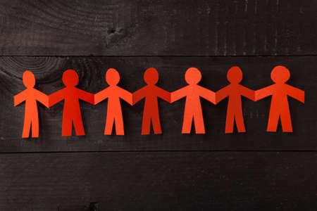 手を繋いでいる紙人形のグループです。チームワークの概念のペーパー クラフト。黒の木製の背景にオレンジ色を人形します。