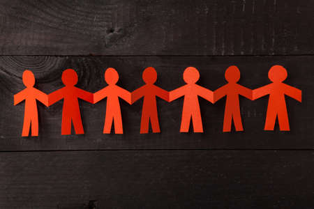Group of paper doll holding hands. Teamwork concept papercraft. Orange dolls on black wooden background Stock Photo