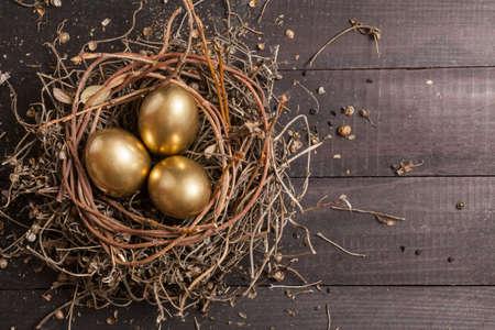 Gouden eieren in het nest op donkere uitstekende houten achtergrond Stockfoto