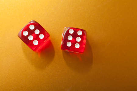 Two red dice on golden background with space for text photo