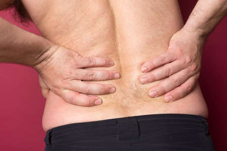 back sprains: Backache concept bending over in pain with hands holding lower back Stock Photo