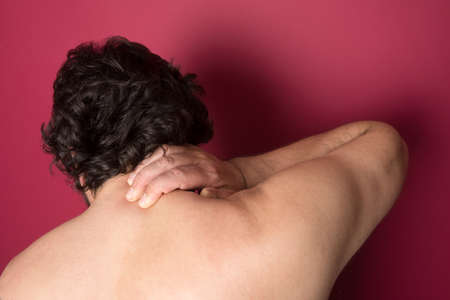 Man suffering from back neck ache, muscle pain photo