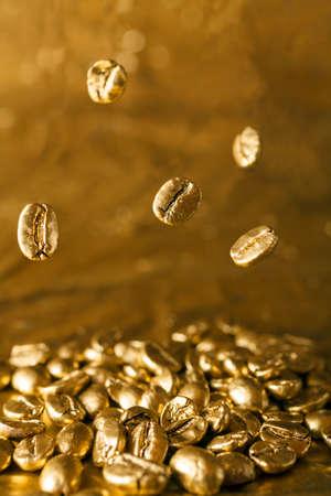 golden bean: Golden coffee beans on golden background falling down