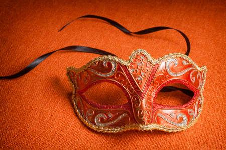 venician: Carnival mask on orange fabric Stock Photo