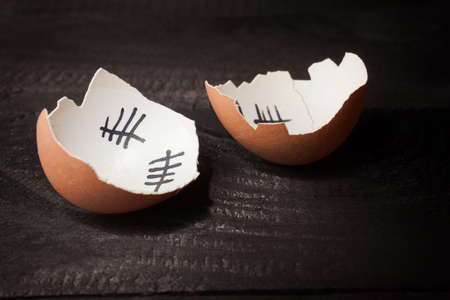 break out of prison: Escape from the egg. Broken egg of chicken that escaped from the egg. Isolated on black wooden background. Stock Photo