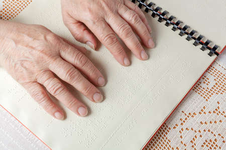 Blind old woman reading text in braille language Stock Photo - 27690197