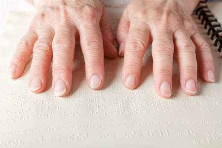 Blind old woman reading text in braille language Stock Photo - 27690195