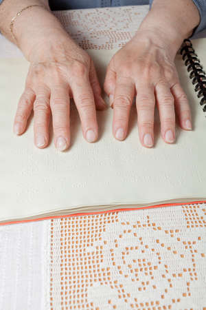 Blind old woman reading text in braille language Stock Photo - 27690202