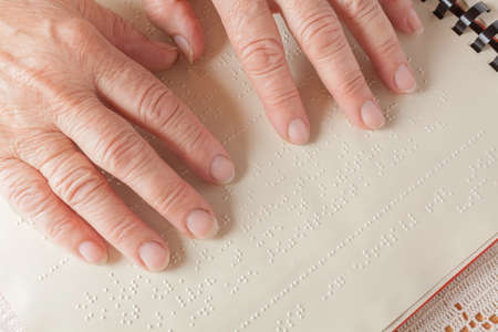 Blind old woman reading text in braille language Stock Photo - 27690283