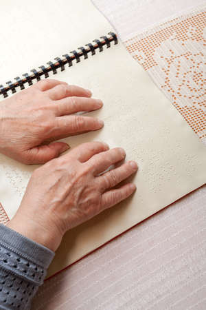 Blind old woman reading text in braille language Stock Photo - 27690280