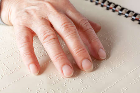 visually: Blind old woman reading text in braille language