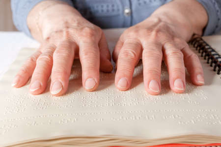 Blind old woman reading text in braille language