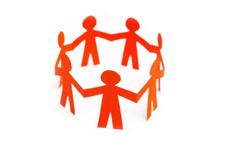 手を繋いでいる紙人形のグループです。チームワークの概念のペーパー クラフトです。オレンジ色の白い背景を人形します。