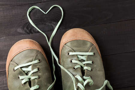 black boards: Heart made of shoelaces. Leather green sneakers on black boards Stock Photo