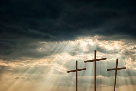Three wooden crosses stand against a dramatic evening sky with radiant beams penetrating clouds Stock Photo