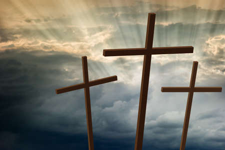Three wooden crosses stand against a dramatic evening sky with radiant beams penetrating clouds photo
