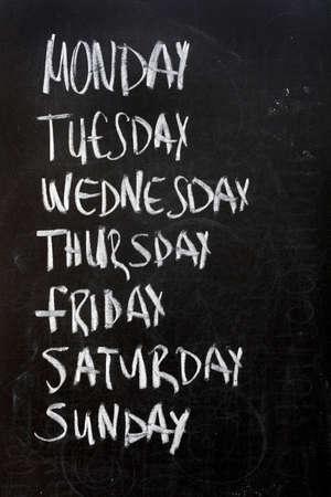 Conceptual weekdays list written on black chalkboard blackboard. Monday Tuesday Wednesday Thursday Friday Saturday Sunday. photo