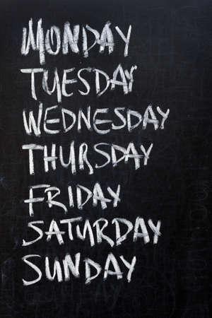 weekdays: Conceptual weekdays list written on black chalkboard blackboard. Monday Tuesday Wednesday Thursday Friday Saturday Sunday. Stock Photo