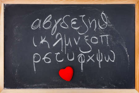 alphabet greek: Twenty four letters of Greek alphabet from alpha to omega (in lower case) handwritten with white chalk on a blackboard with red heart