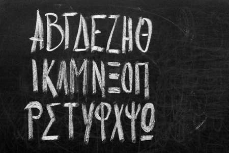 greek alphabet: Twenty four letters of Greek alphabet from alpha to omega (in upper case) handwritten with white chalk on a blackboard