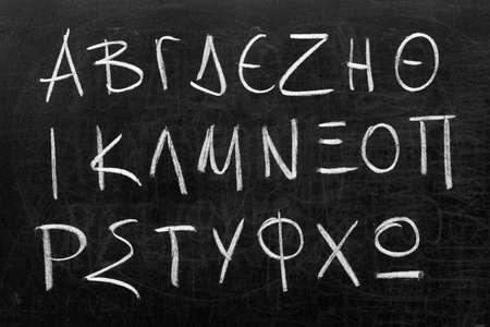 alphabet greek: Twenty four letters of Greek alphabet from alpha to omega (in upper case) handwritten with white chalk on a blackboard