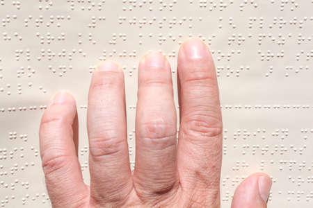 点字テキストを読む男性の手のクローズ アップ