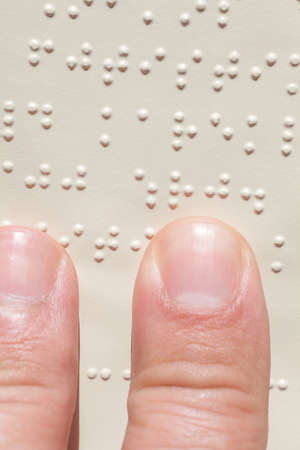 Close up of male hand reading braille text Stock Photo - 28027399