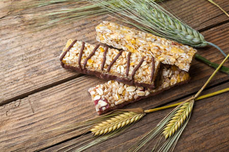 Cereal bars and dry wheat on a wooden table Stock Photo