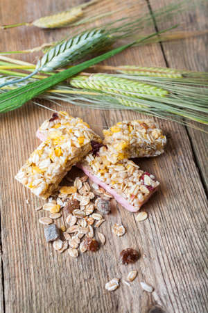 Cereal bars and dry wheat on a wooden table photo
