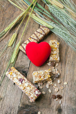 Cereal bars and dry wheat and a red heart on a wooden table photo