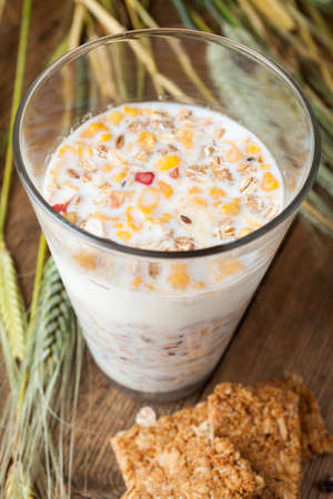 Muesli within a glass of milk, cereal bars and dry wheat on wooden table photo