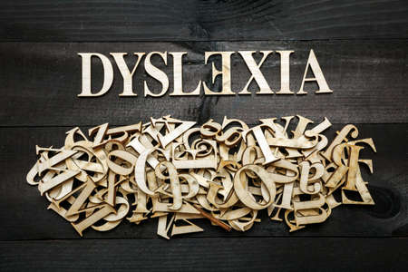 dyslexia: Dyslexia word with wooden letters on dark background Stock Photo