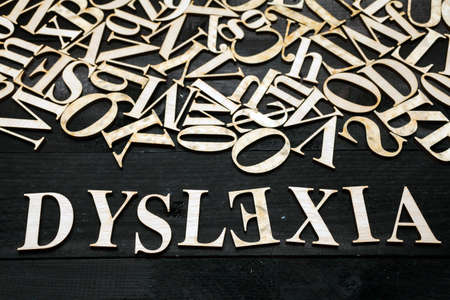暗い背景に木の手紙と「失読症」単語