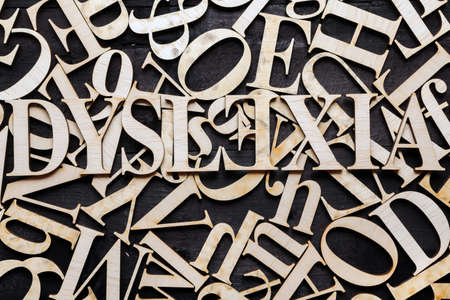 Dyslexia word with wooden letters on dark background Stock Photo
