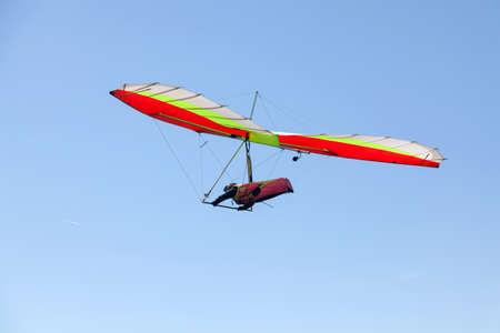 非常に明確な晴れた日のギリシャの山の上を飛んでのハング グライダー