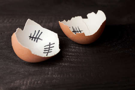 break out of prison: Escape from the egg. Broken egg of chicken that escaped from the egg. Isolated on black wooden .
