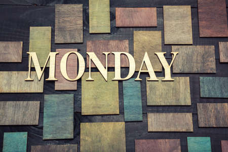 Wooden letters forming word MONDAY written on wooden background photo