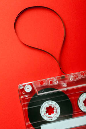 Old Cassette with Tape Unwound on red background photo