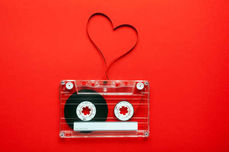 tape cassette: Vintage audio cassette with loose tape shaping a heart on red background