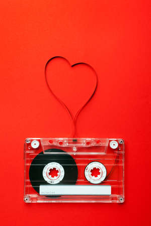 single songs: Vintage audio cassette with loose tape shaping a heart on red background