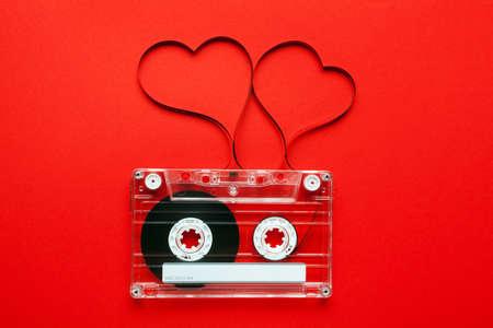 Vintage audio cassette met losse tape vormgeven twee harten op rode achtergrond